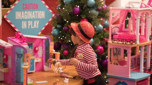 Little girl playing with a Barbie DreamHouse.