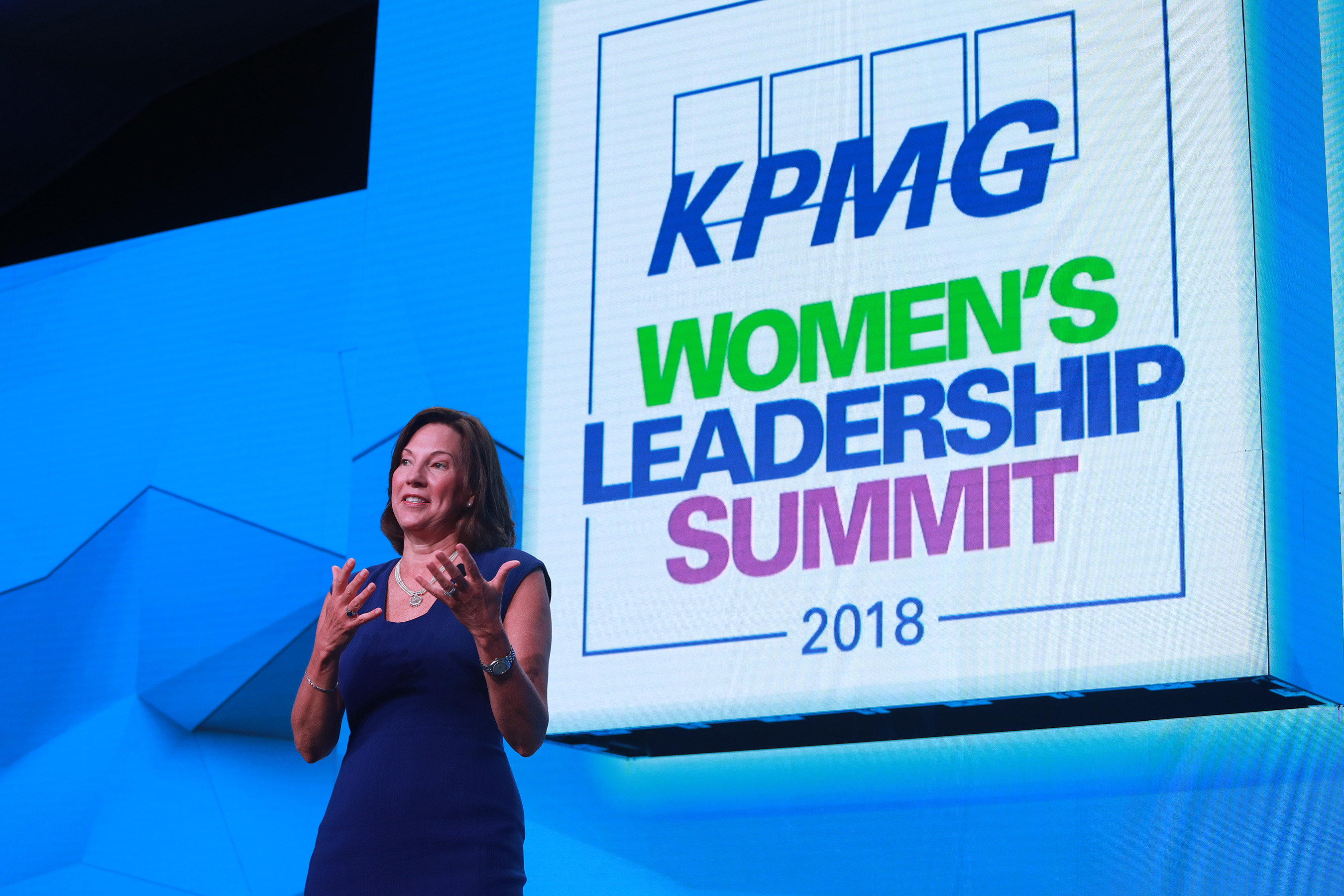 Lynne Doughtie, KPMG US Chairman and CEO standing on a stage in front of a big blue screen.