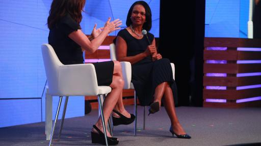 Michele Tafoya and Dr. Condoleezza Rice sitting on a stage in chairs talking.