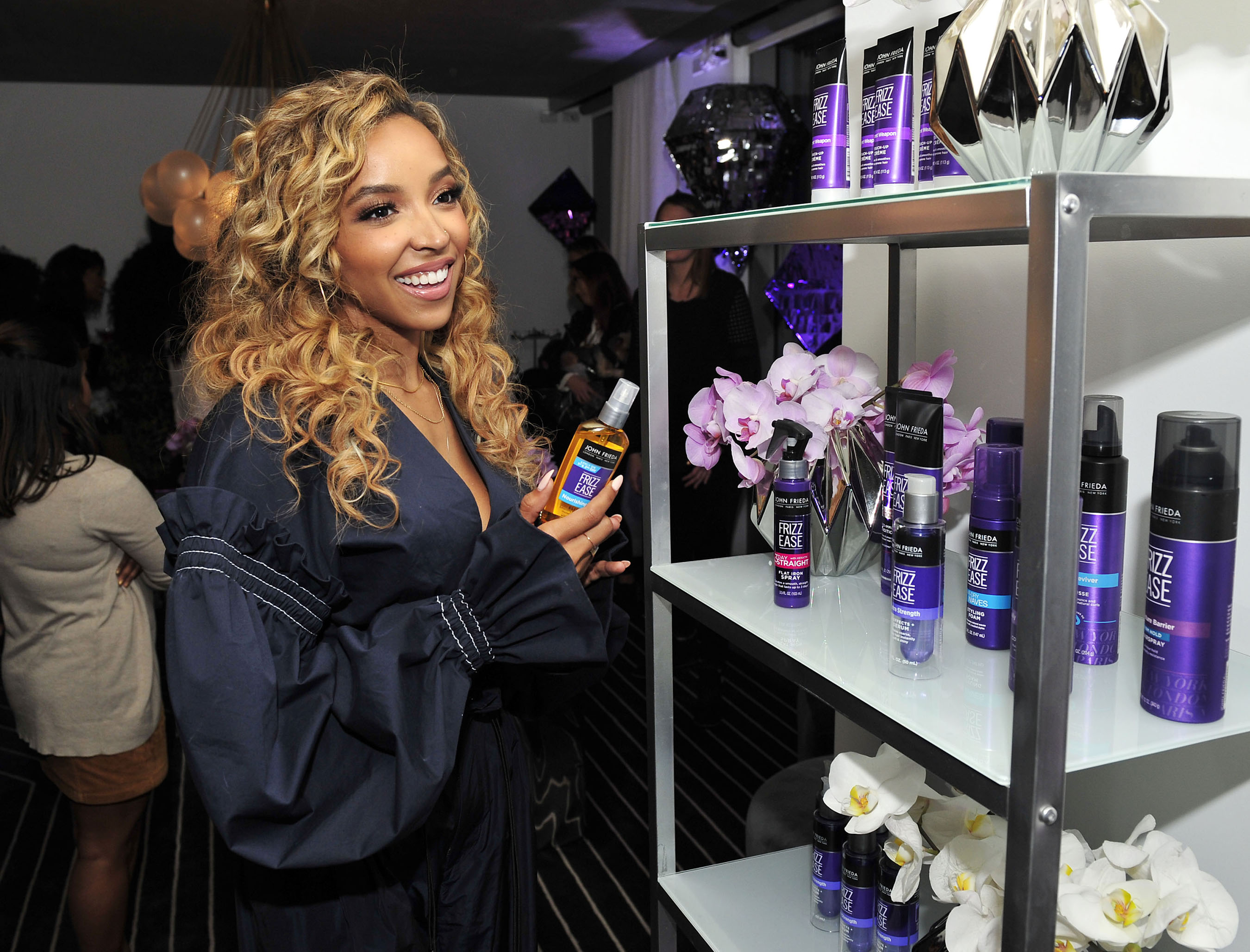 Tinashe checks out the John Frieda® Hair Care Frizz Ease® products on display