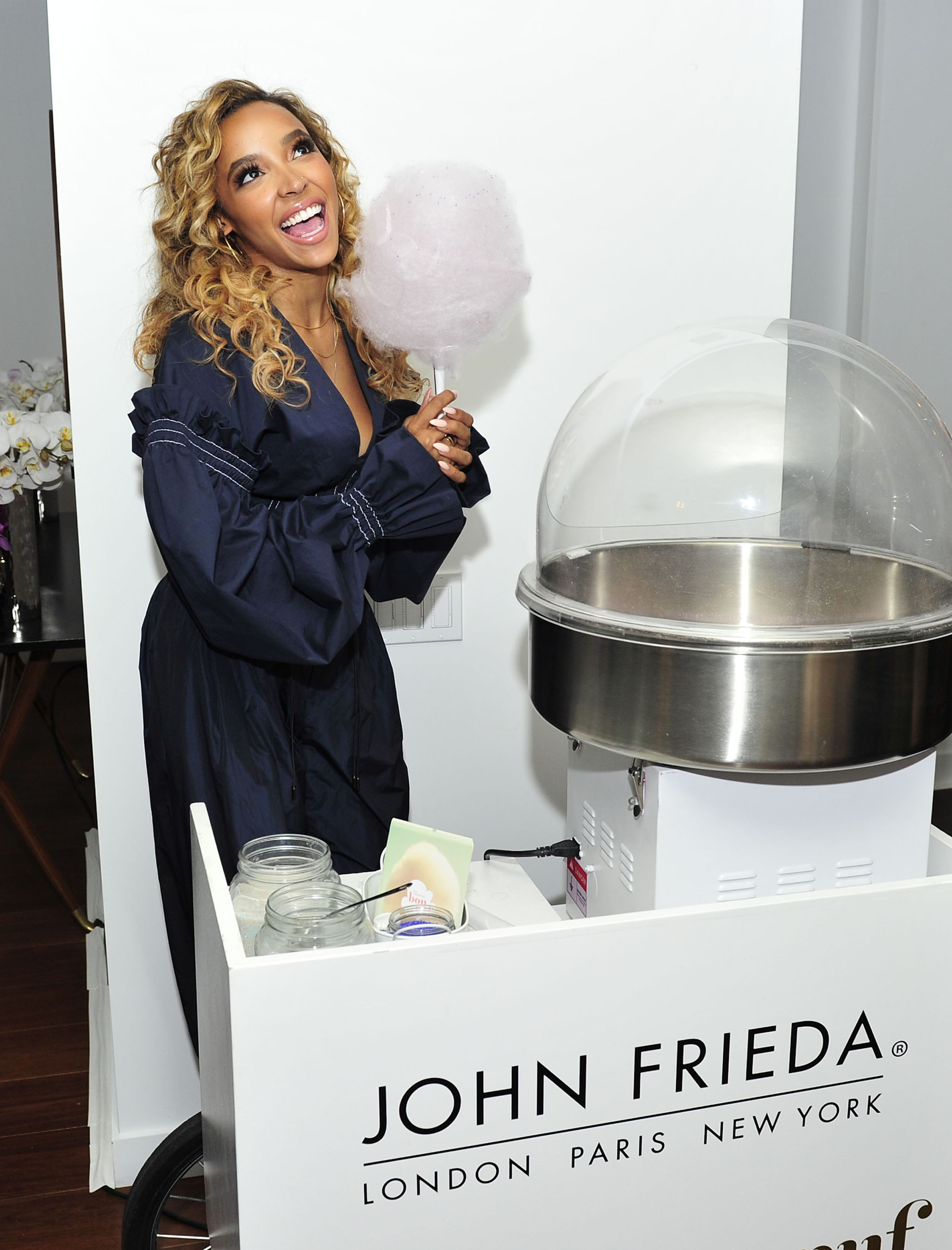 Tinashe helps serve cotton candy at the John Frieda® Hair Care Frizz Ease® event in LA