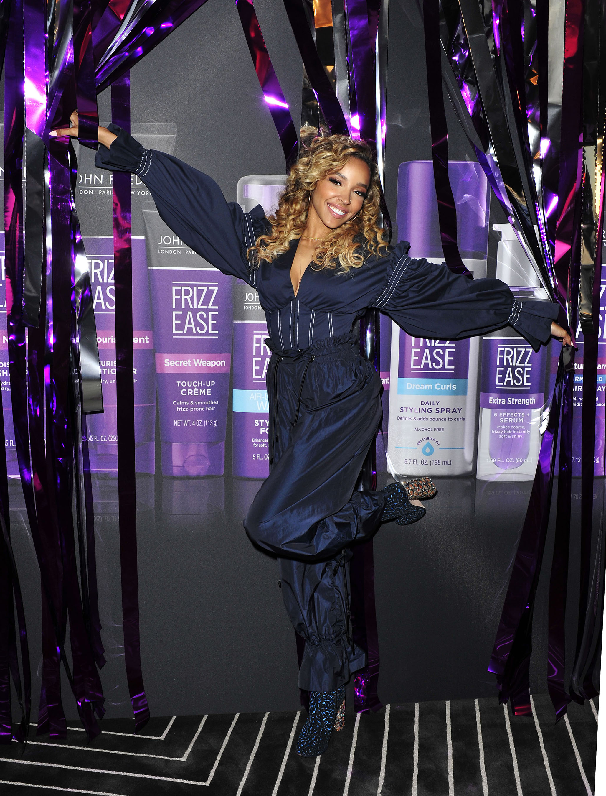 Tinashe poses in front of the festive John Frieda® Hair Care step and repeat
