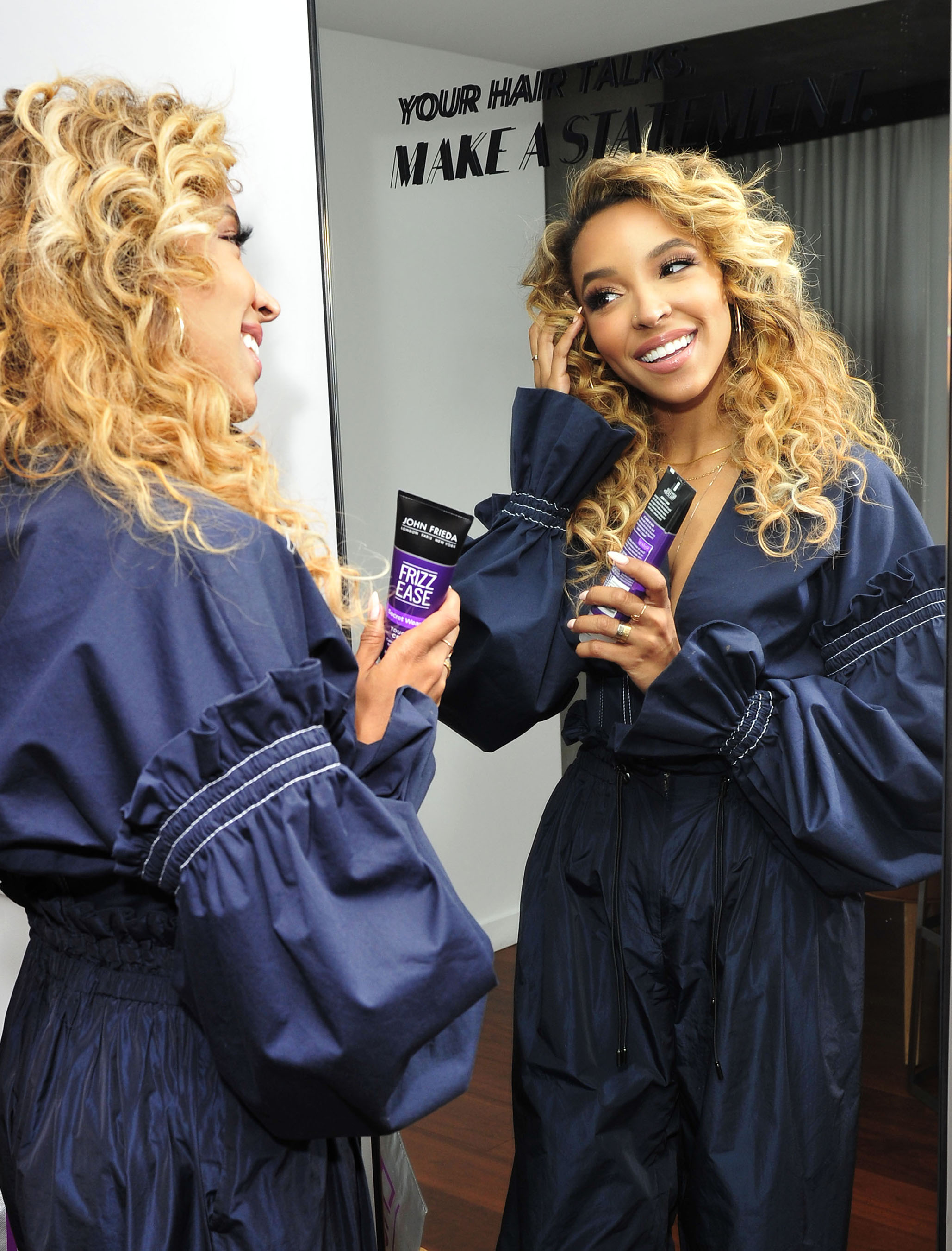 Tinashe touches up her curls before the John Frieda® Hair Care event in LA