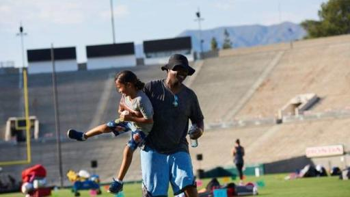Father carrying daughter on the field of the Rose Bowl Stadium