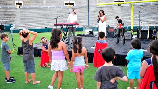Children watch Us the Duo perform at Campout