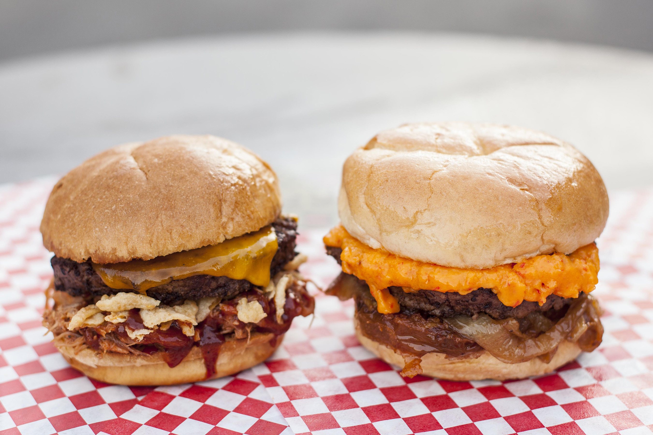 Georgia vs Oklahoma burgers - Both burgers feature a half-pound burger, but the Oklahoma burger features American cheese, crispy onions, and BBQ pulled pork, while the Georgia burger is topped with pimento cheese, fried green tomatoes and grilled onions.