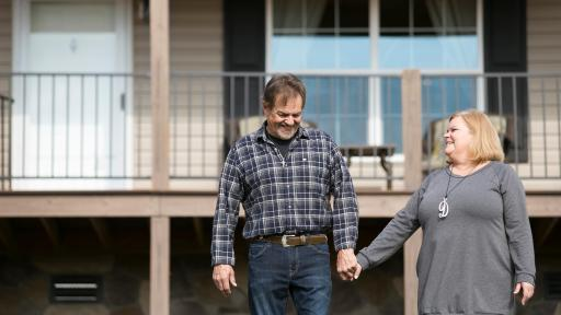 The Wood couple standing in front of home