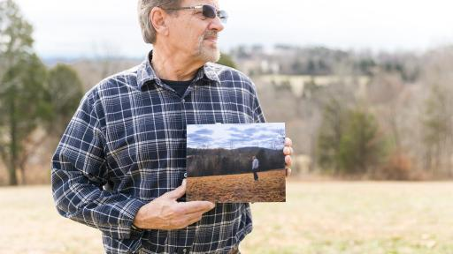 Mr. Wood holding a photo of a man standing in the same field as he currently is