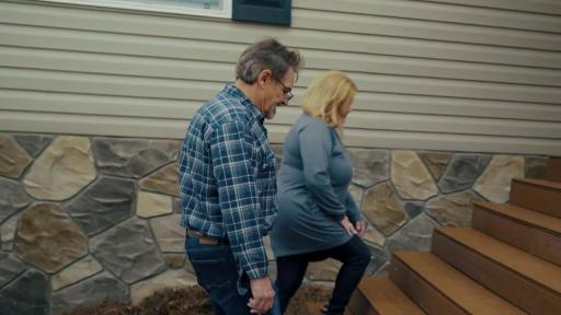 Man and woman walking up steps to new home.