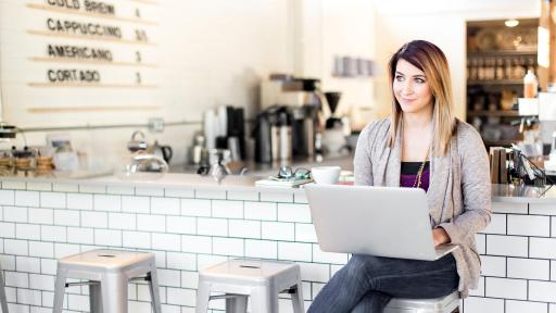 Woman with laptop sitting at a counter.