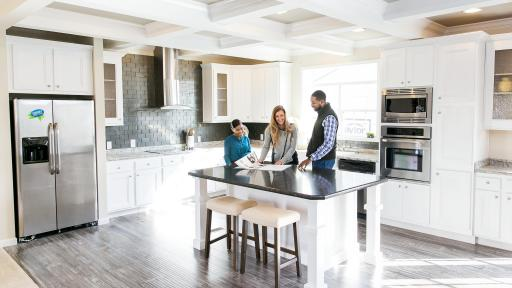 A couple looks over papers atop a counter in a brand new kitchen.