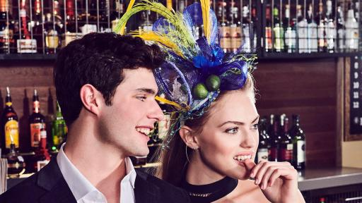 Man in black suit leaning against the bar, holding a margarita. A woman in a black dress wearing a margarita-inspired bonnet leans next to him.