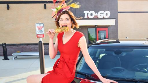 Woman in a red dress wearing a rib-inspired bonnet eating ribs while sitting atop a red car.