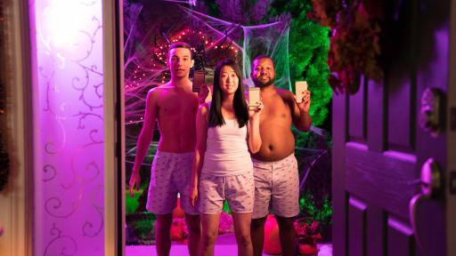 Two males, shirtless in Chili's boxers and one female wearing a white tank top and Chili's boxers at the entrance of a house for Halloween