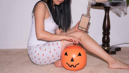 Girl holding a cardboard phone and sitting next to a pumpkin bucket