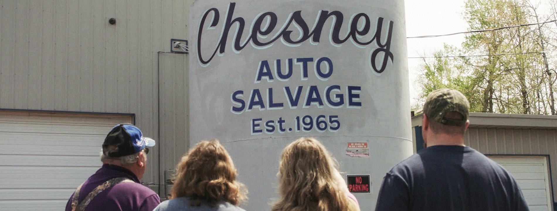"Hand-painted sign for Business that reads ""Chesney Auto Salvage""."