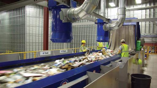 Recycling materials being dumped into a large conveyor belt