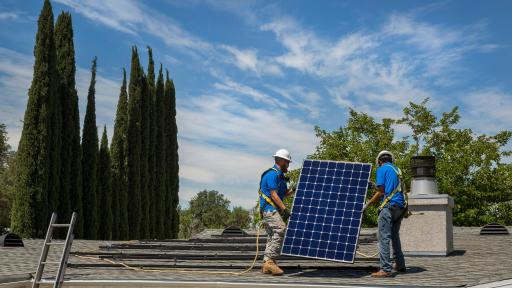 Two SunPower techs installing solar panels on a roof