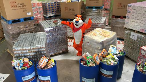Tony the Tiger surrounded by donated food collected for food drive