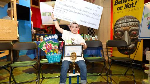 Hunter Hamm, winner of the 2018 Rotten Sneaker Contest, holding the prize check above his head.