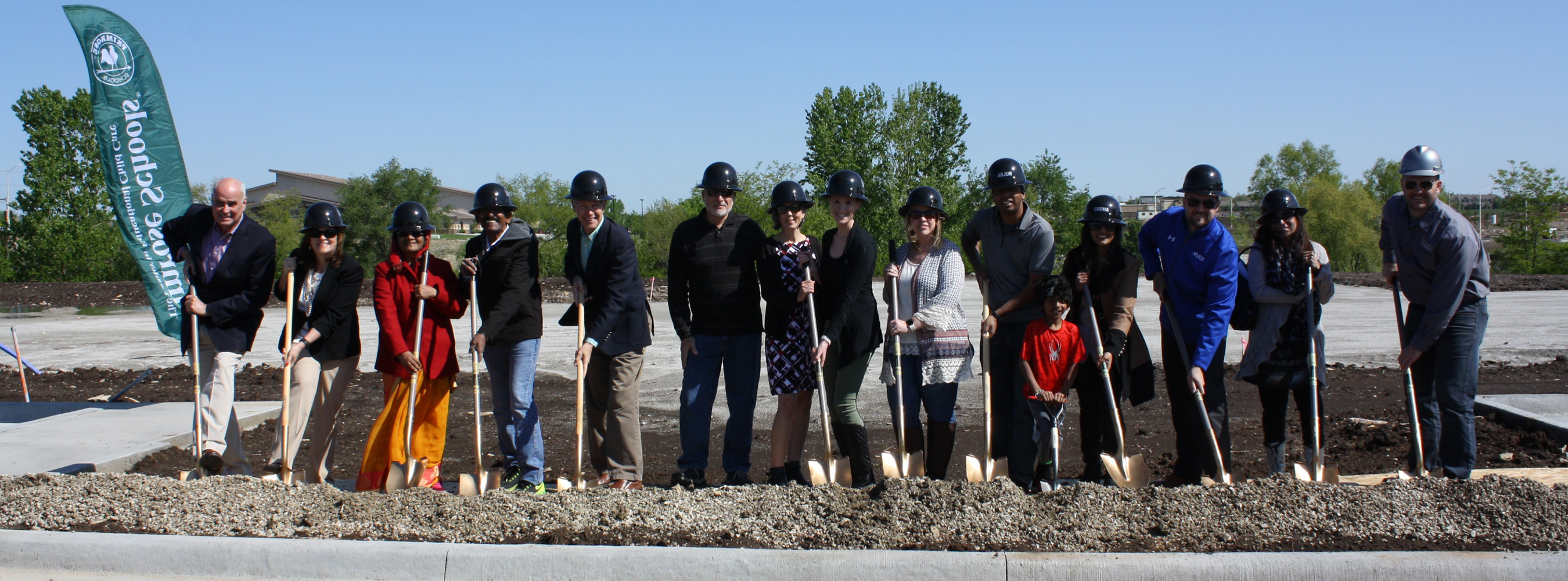 Banner image of group of people breaking ground on new construction site with shovels