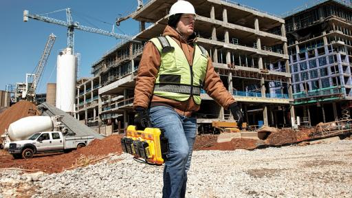 A man carrying the 4-port Charger in front of a construction site.