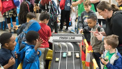 Children watching toy cars race down a track towards the finish line