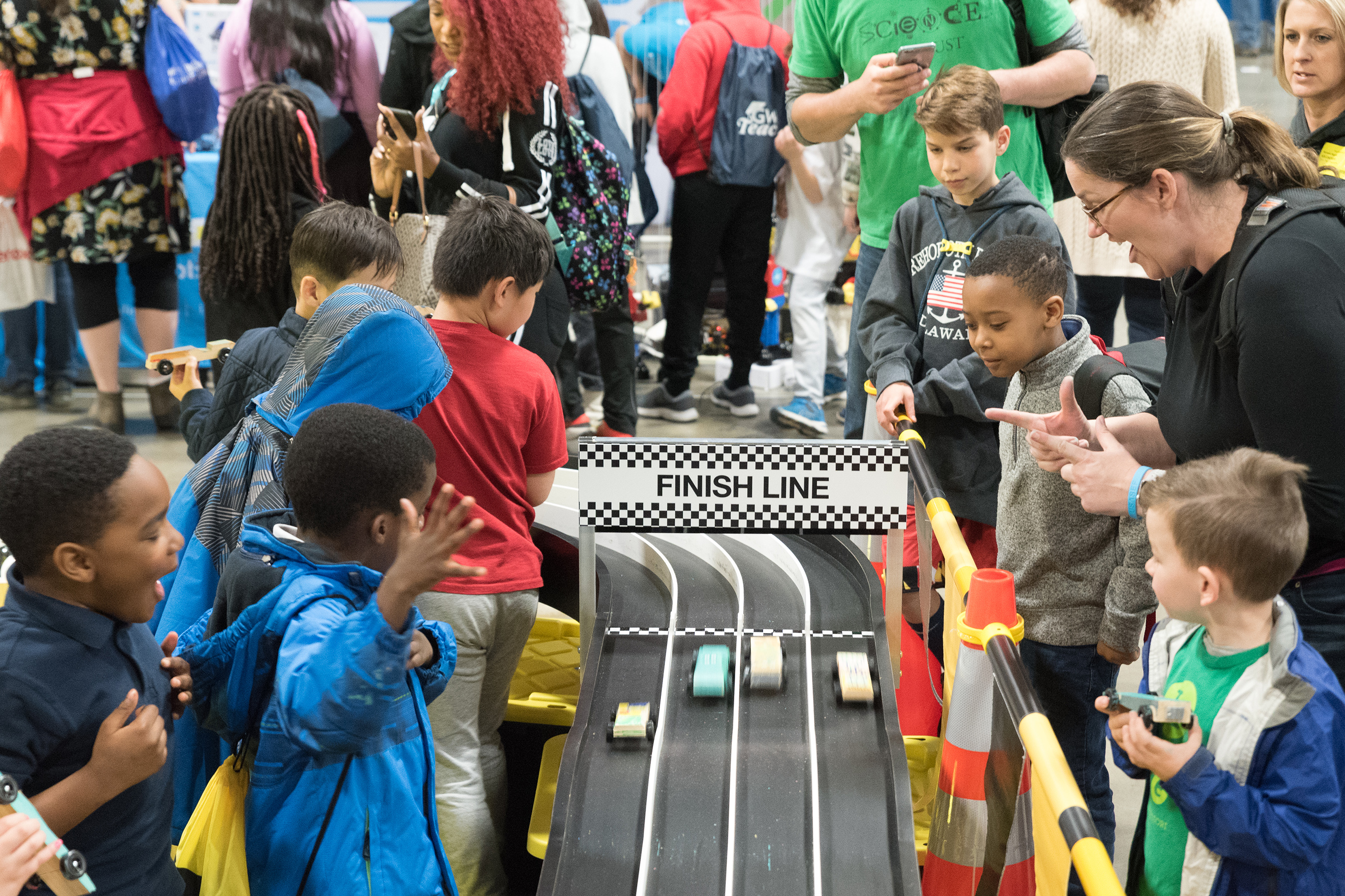 Excited children witness their car creations in action at Stanley Black & Decker's traveling makerspace.