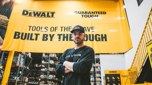 "Brian Steorts standing with arms crossed beneath a large yellow banner. The banner has the DeWalt logo, a guarantee of toughness, and the slogan, ""Tools of the brave, built by the tough."""