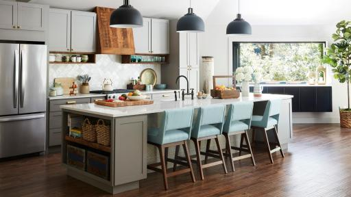 A modern kitchen with hanging lights, decorative island lined with chairs, and wood floor.