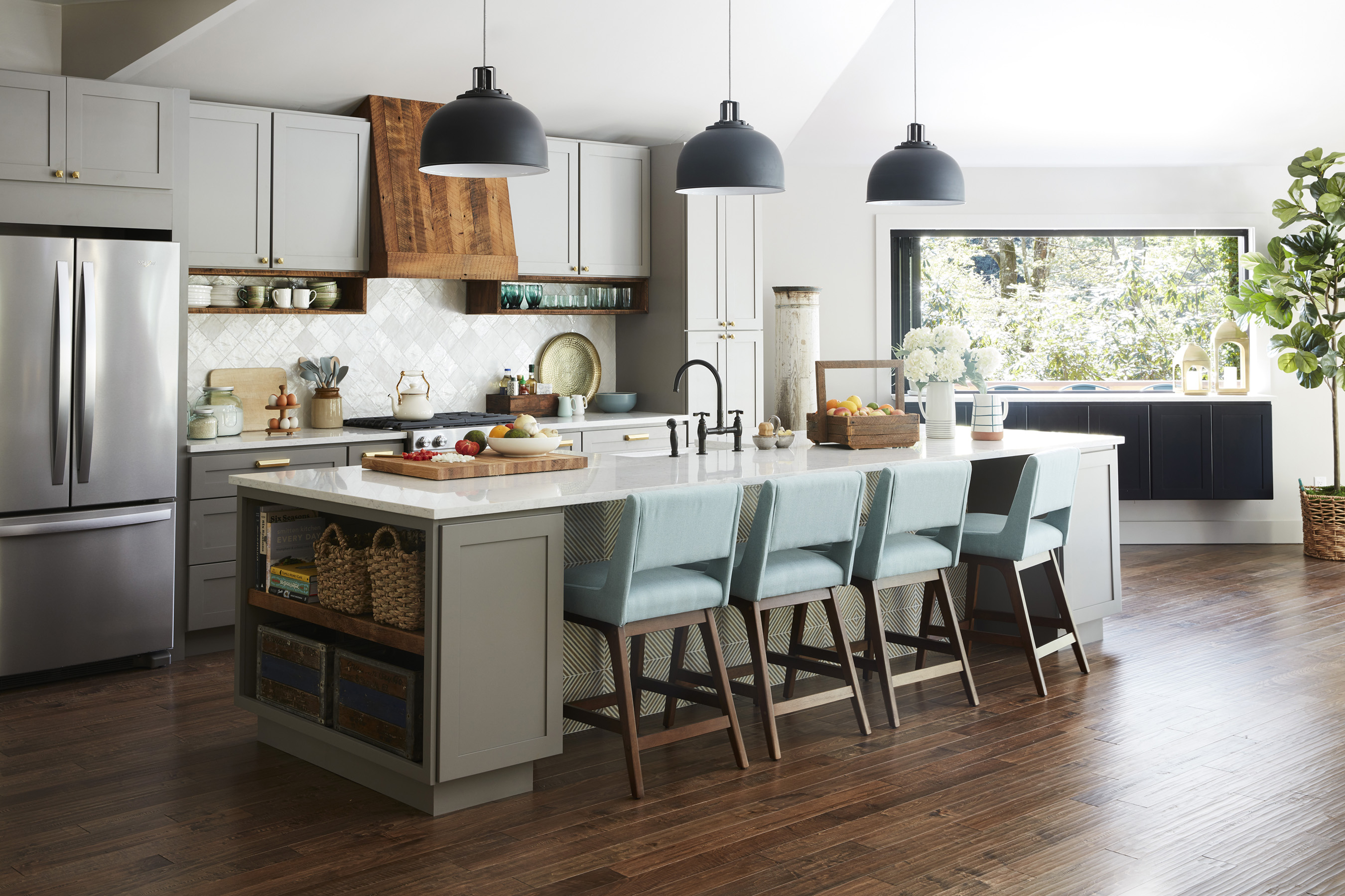 Rustic details and refined modern style combine to give DIY Network Ultimate Retreat 2018 a spacious kitchen that is functional and good-looking at the same time. A 12-foot island with seating for four serves as the focal point, and durable quartz countertops provide an easy-to-clean workspace that is bright and airy, augmented by three oversize lights and tall, vaulted ceilings above. Touches like a hood and dish boxes made of reclaimed wood add a handcrafted feel, while the floating buffet with a folding accordion window that passes through to the bar outside adds some truly unique functionality.