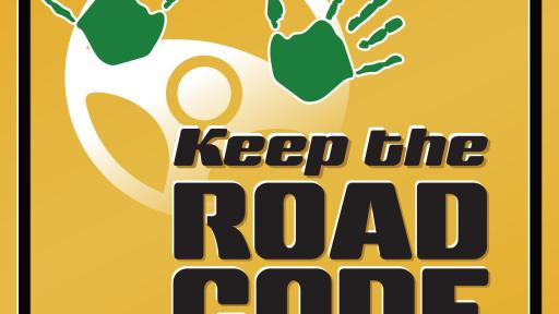 "Yellow badge with green hands on a steering wheel and text that reads ""Keep the Road Code"""