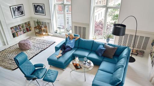 Woman lounging on blue leather sectional