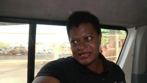 African woman on a bus talking to the camera