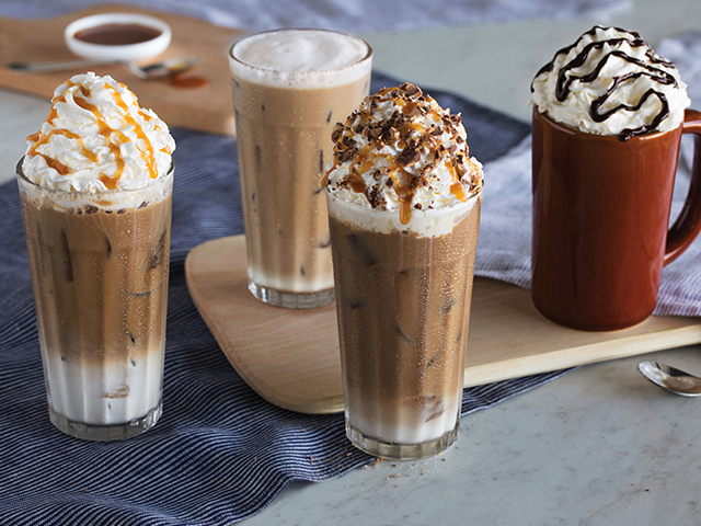 four coffee drinks some with whip cream, chocolate and caramel toppings