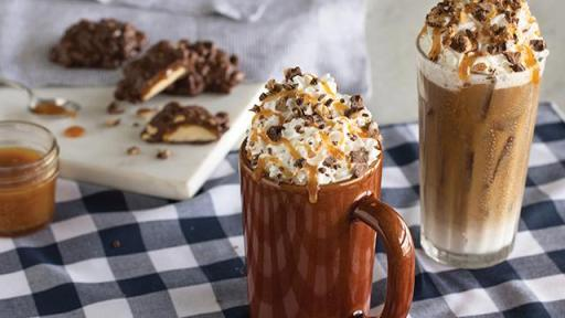 Two latte drinks with whip cream, caramel and chocolate toppings