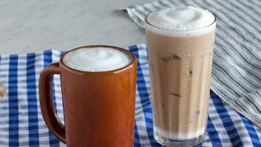 A hot latte and an iced latte sit on a checkered tablecloth.