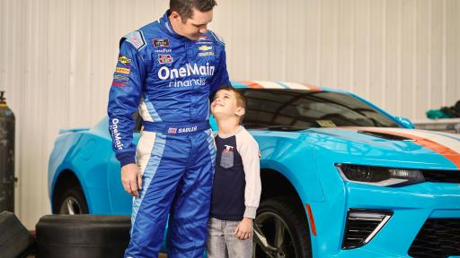 NASCAR Driver Elliott Sadler and son, Wyatt stand by blue race car