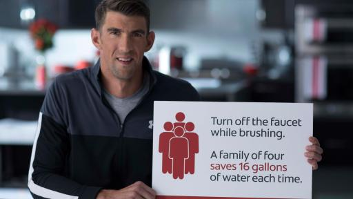 "Michael Phelps holding up a sign that says ""Turn off the water while brushing. A family of four saves 16 gallons of water each time."""