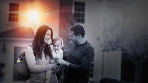 Couple holding baby in from out house with sun shining