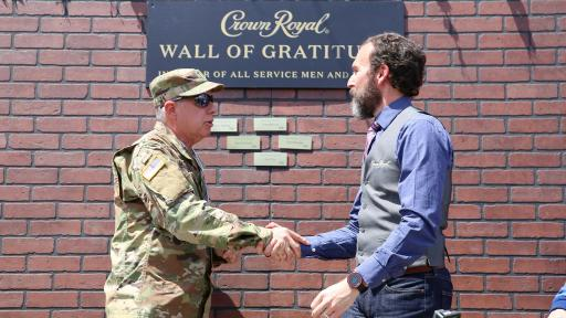 Solider and man shaking hands in front of appreciation wall