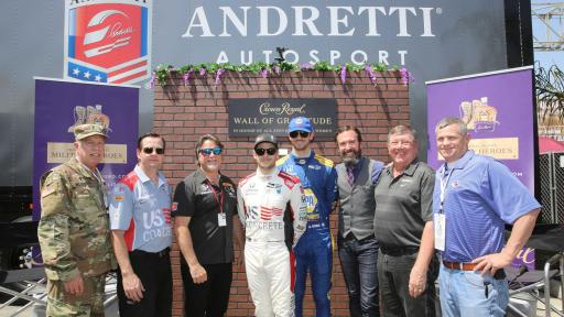 8 men in front of Wall of Gratitude by Crown Royal and Andretti AutoSport