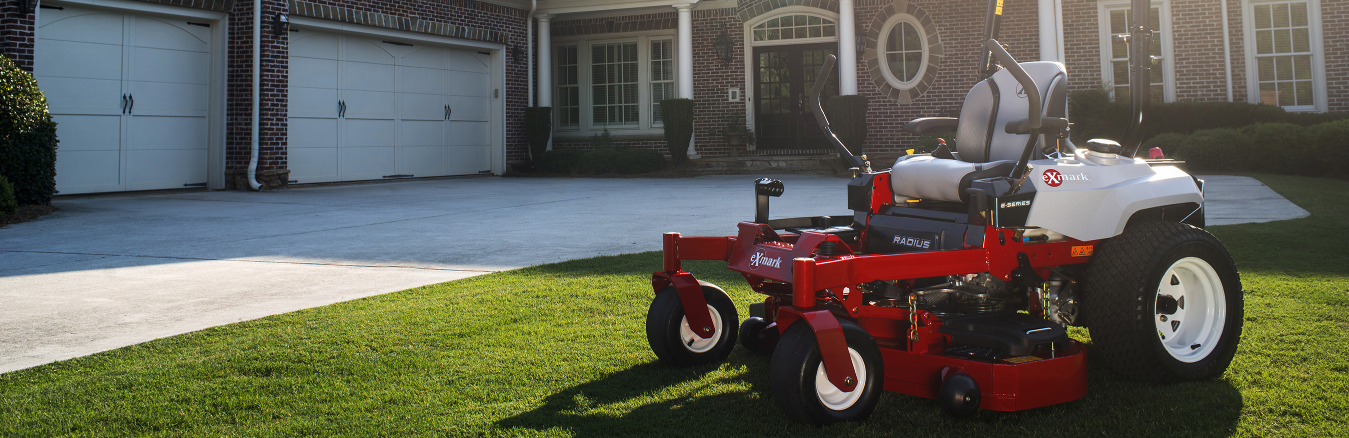Red Exmark lawn mower parked on grass in yard of large brick house