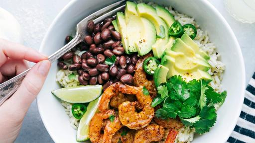 A bowl of shrimp beans and avocado on top of rice.
