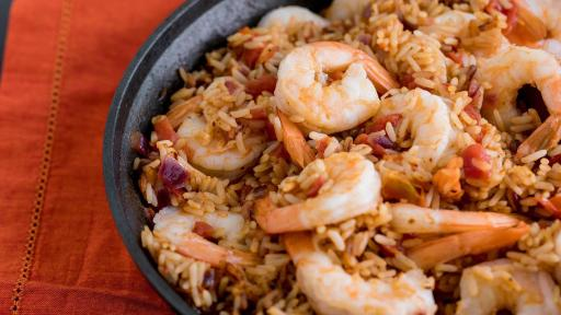 A black bowl on a red tablecloth with seasoned rice and shrimp.