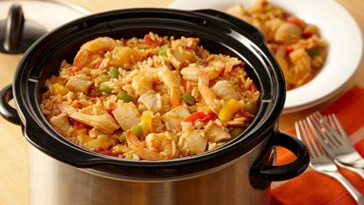 Crockpot filled with chicken, shrimp, rice and minced vegetables.