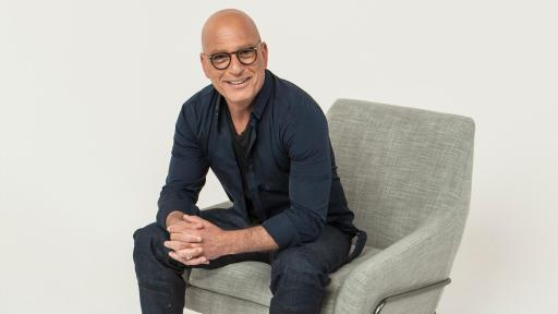 Howie Mandel in glasses sitting on a chair with red shoes among a plain gray background