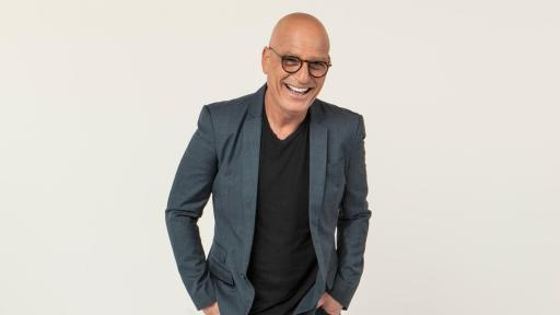 Howie Mandel with glasses standing in a suit