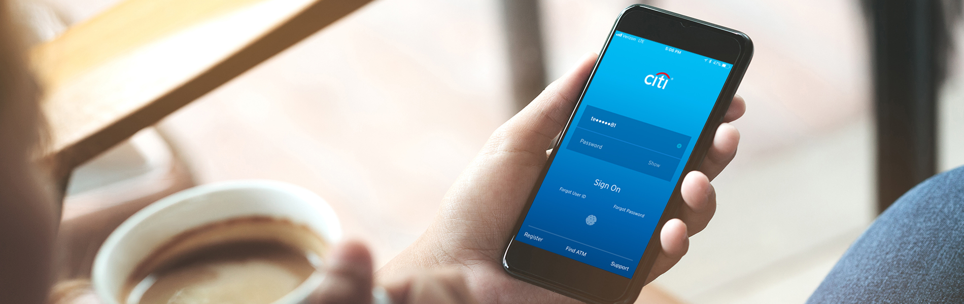 A person holding a smartphone with the Citi mobile banking app open.