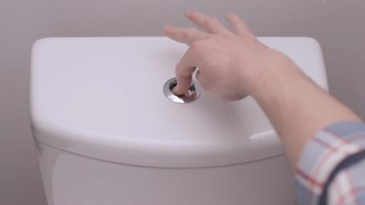 A hand is reaching to flush a white toilette.